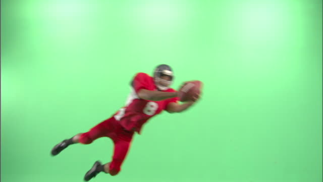 WS, American football player diving and catching football ball in studio
