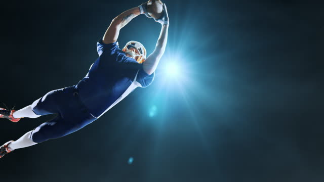 American football player jumps with a ball