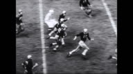 American football players executing a touchdown play / referree fires gun / crowds in stands go wild