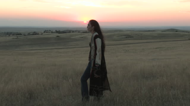 MS PAN American Indian young woman standingon great plains in grass near at sunset time / Pine Ridge, South Dakota, United States