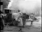 American jeeps on fire / soldiers moving wounded on a stretcher near jeeps / soldiers carrying wounded man on stretcher past wrecked vehicles