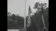 American sailor and soldier raise flag on flagpole in Shiroyama Park during centennial celebration of Commodore Matthew Perry's landing in Japan /...