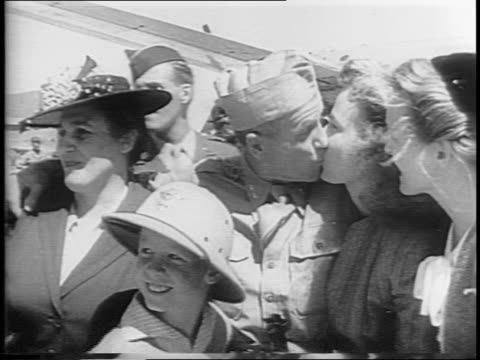 American soldiers disembark from an airplane and are greeted by their loved ones soldier kisses two women / General Carl Spaatz exits the airplane...