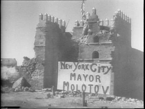 American soldiers marching into formation / bombed building with handmade 'New York City Mayor Molotov' sign flying American flag / soldiers and...