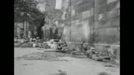 American soldiers run through open areas in Nuremberg and lay prone / a tank drives past skeleton of ruined buildings / soldiers firing mortars in...