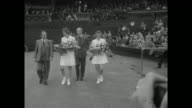 MS American tennis players Doris Hart and Shirley Fry holding bouquets and tennis rackets walk across court at Wimbledon with escorts / CU photo op...