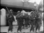 American troops march and stand at attention in Tunis at train station / exVichy French officer salute American officers
