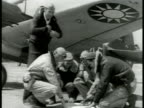 American Volunteer Group's pilots under wing of airplane going over map behind one pilot w/ Nationalist Chinese jacket mechanic by engine checking...