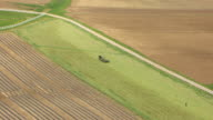 WS AERIAL Amish farmer with horse and cart riding through field / Kentucky, United States