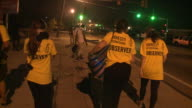 KTVI Amnesty International Observers Wearing Dust Masks Walk Toward Riot Police on August 18 2014 in Ferguson Missouri Protests and riots broke out...