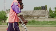 Amputees on crutches play soccer on a dusty field in Ghana. Available in HD.