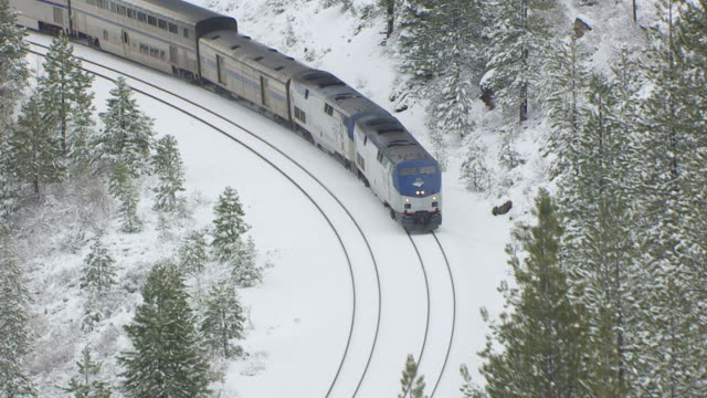 MS TS AERIAL POV Amtrak locomotives pulling passenger train passing through snow covered pine forest at Donner Pass in the northern Sierra Nevada / Truckee, California, United States