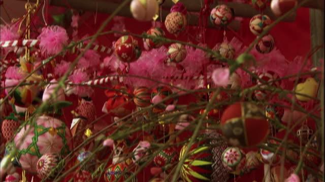 An abundance of gorgeous Hina Matsuri decorations, tilting down to the face of a doll girl.