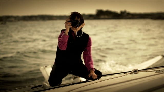 An active female pensioner while taking pictures on a trimaran in the backlight