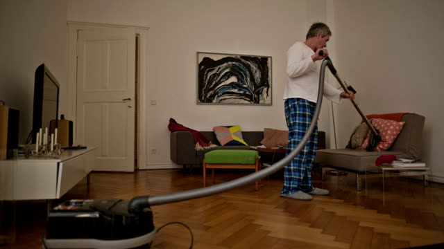 An active senior man during vacuum cleaning in his old Berlin apartment