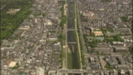 An aerial view of Kyoto, Japan, reveals the Kamo River, urban areas, and the woods surrounding the Upper Kamo Shrine.