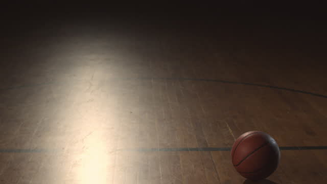 A male basketball player dribbles a ball on a gym court and then drops the ball and walks away.