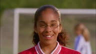 An African American girl wearing glasses and a soccer jersey smiles.