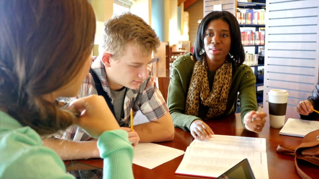 An African American young woman teaches or tutors a group of home school high school students in public library