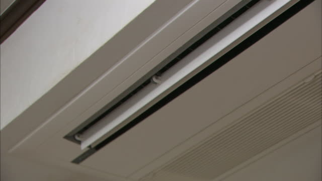 An air  conditioner vent slowly opens.
