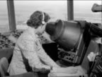An air traffic controller looks into a radar device at London Airport