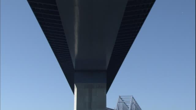 An airplane flies above the Tokyo Gate Bridge as a boat sails beneath.