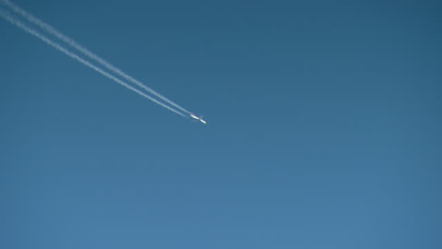 An airplane leaves contrails in a blue sky.