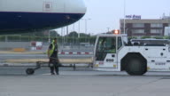 An airport worker disconnects aircraft from tug ready for final flight out of Heathrow's terminal one a BA service to Hanover The building at one...