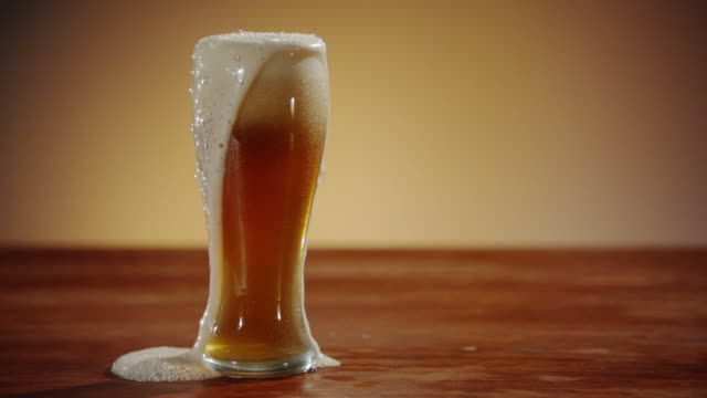 An Amber Ale overflowing from Glass