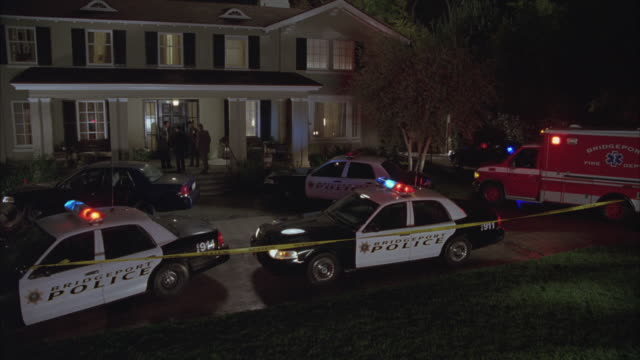 An ambulance and several police car bizbars flash in the driveway of an upper-class home.