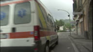An ambulance cruises through a nice neighborhood near the mountains.