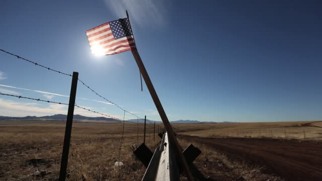 An American flag flies on the USMexico border fence after being placed there by a local rancher Border Patrol Vehicle drives at sunset Border Patrol...