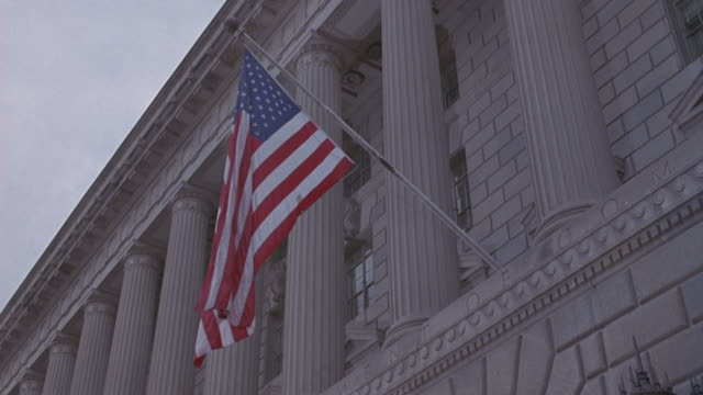 An American flag hangs from a government building in Washington, D.C.