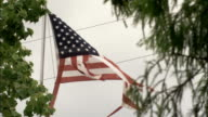An American flag is torn by damaging winds. Available in HD.