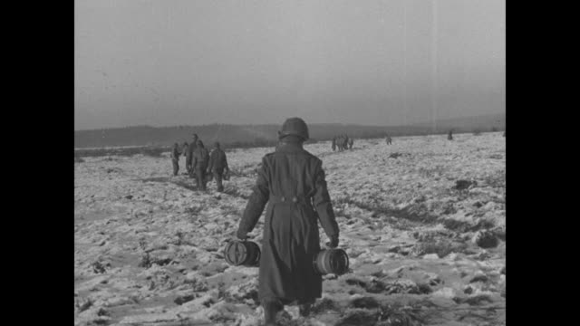 VS an American soldier places mine and covers it man follows other GIs holding land mines / VS men scrape snow over mine and place them in muddy...