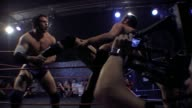 An American style professional wrestling match sequence with cameraman filming in foreground