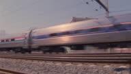 An Amtrak train speeds by on train tracks.