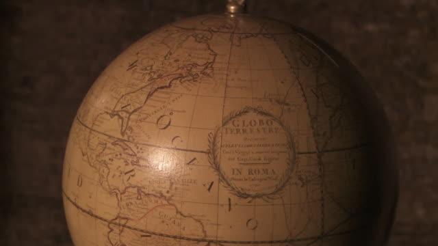 An antique globe is spun.
