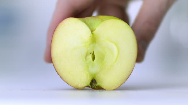 An apple placed on a white chopping board being held by hand and sliced very finely
