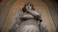An arch surrounds the statue of an angel at Genoa's Monumental Cemetery of Staglieno. Available in HD.