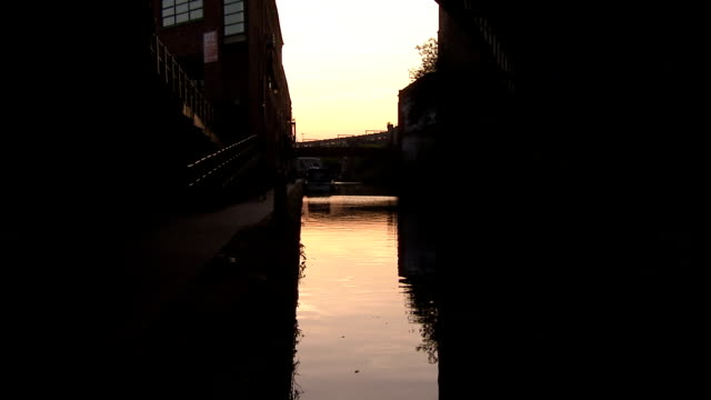 An arched stone bridge stretches across the calm waters of Bridgewater canal at sunset. Available in HD.