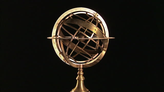 An armillary sphere slowly spins in front of a black background.