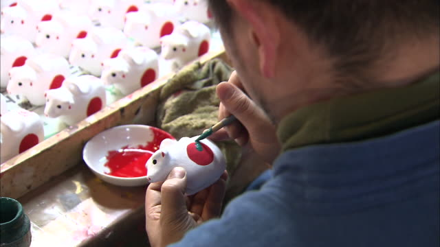 An artisan paints a clay ox figurine at a ceramics shop in Chofu, Tokyo.