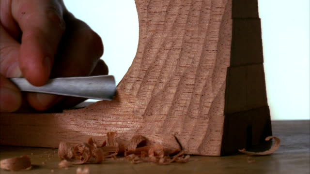 An artisan uses a chisel to make a wood sculpture. Available in HD.