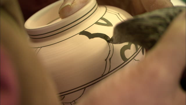 An artist paints a finely detailed design on a piece of pottery.
