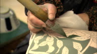 An artist paints green glaze onto a ceramic vase.