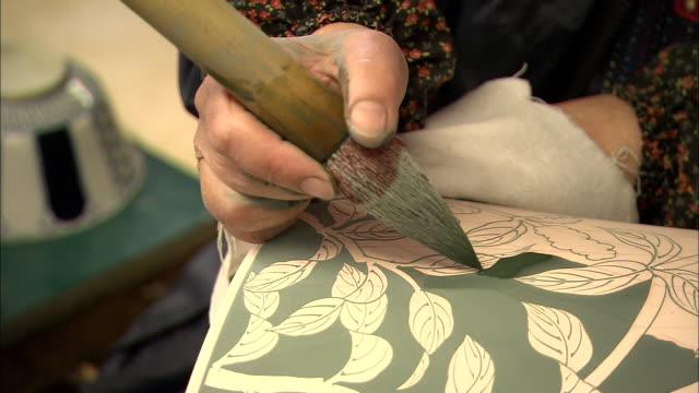 An artist paints green glaze onto a ceramic vase.