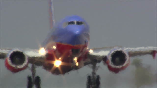 An ascending airliner closes its landing gear after take-off from LAX International Airport.