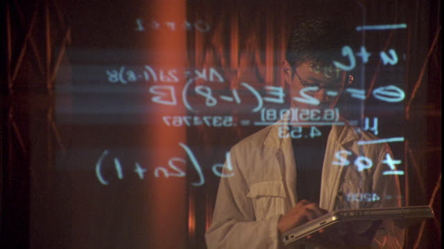 An Asian man uses a touch screen tablet while looking at a display of mathematical equations on a transparent screen.