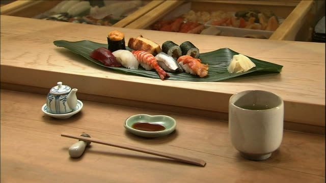 An assortment of sushi lies on the counter of a sushi shop.